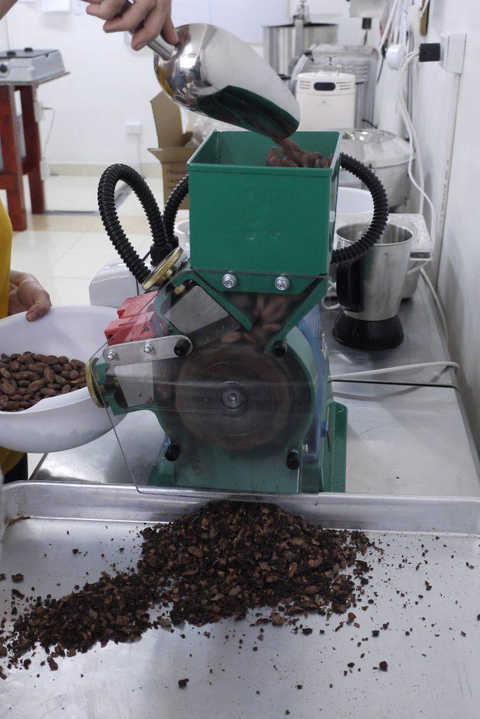 Yoshiris Peña Monasca schält Kakaobohnen mit Hilfe dieses Gerätes in der Oro Moreno Schokoladenmanufaktur. Foto: ForestFinance