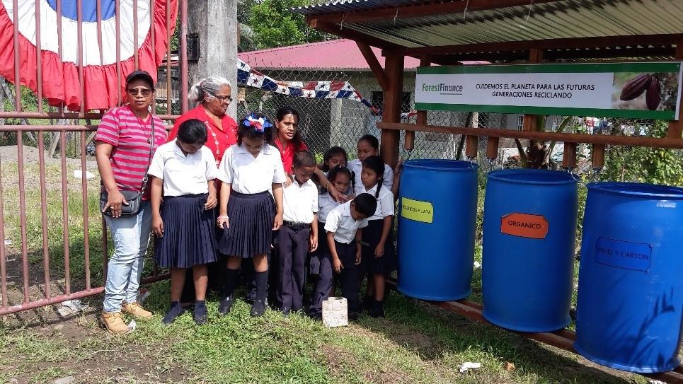 Cecilia Morales, Angestellte beim ForestFinance-Dienstleister Barca, zuständig für einige unserer Flächen in Bocas del Toro, (links im Bild) mit SchülerInnen der New Paradise School, Panama vor Mülltonnen zur Mülltrennung im Jahr 2018. Wir fördern in der Region zahlreiche Programme zum Umweltschutz und zur Erhöhung der Lebensqualität.